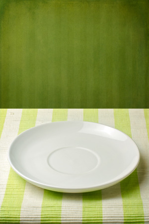 Empty plate on striped tablecloth over green vintage wall photo