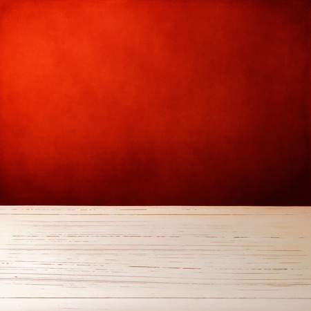 surface: Background with white wooden table and grunge red wall Stock Photo