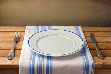 Empty plate with fork and knife on tablecloth on wooden table over grunge background