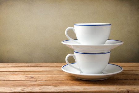 tabletop: Two coffee cups on wooden tabletop against grunge background Stock Photo
