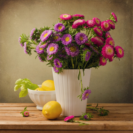 Beautiful aster flower bouquet with lemons on wooden table