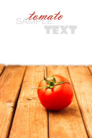 Single tomato on wooden table over white background