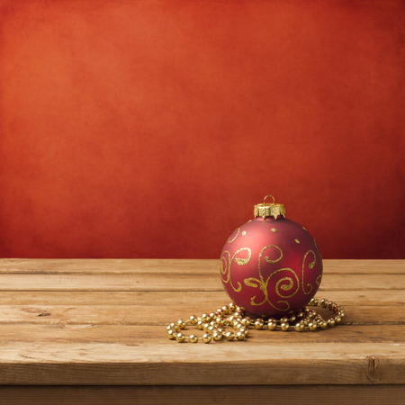 Christmas ornament on wooden table over red grunge background photo