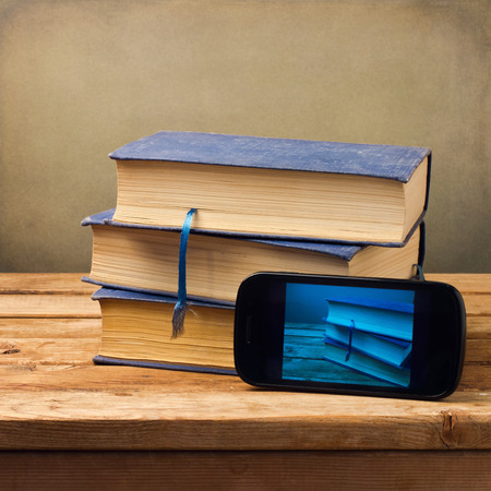 Old books and modern phone with picture on wooden table