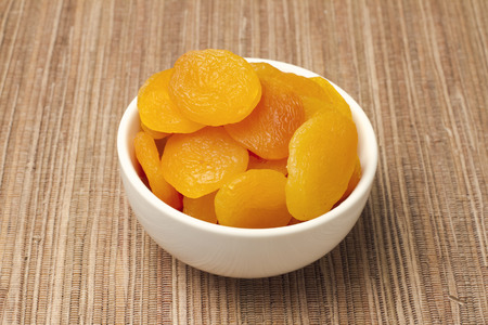 Dried apricots in white dish on tablecloth