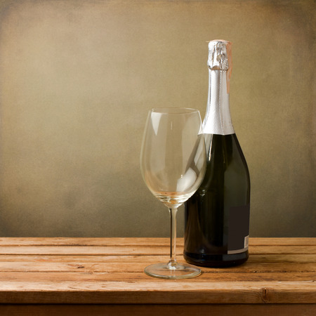 Bottle of wine with empty glass on wooden table