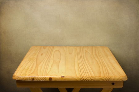 table: Background with wooden table over grunge wall Stock Photo
