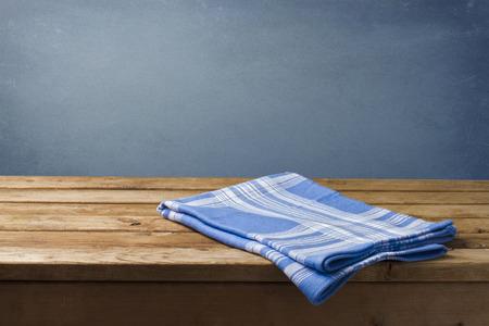 napkin: Fondo con la mesa de madera, mantel y la pared azul del grunge