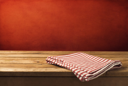 table: Background with wooden table, tablecloth and  grunge red wall Stock Photo