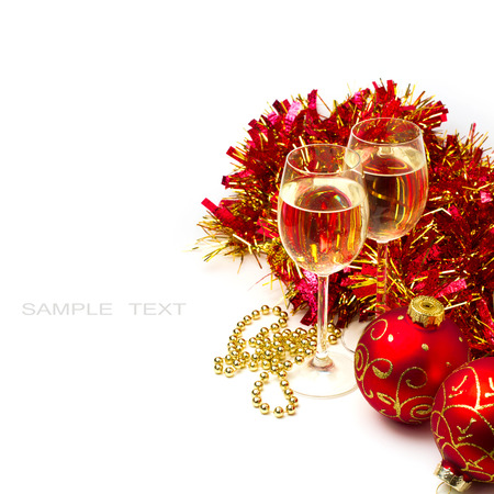 Christmas background with glasses of wine and ornaments over white