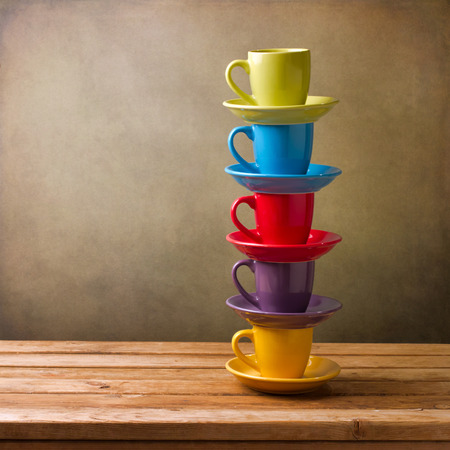 Colorful coffee cups on wooden table over grunge background