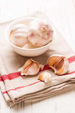 tabletop: Garlic in white dish on white wooden tabletop Stock Photo