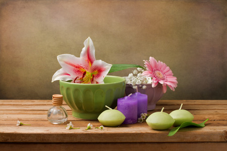 Still life with flowers and candles on wooden table photo
