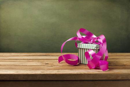 Small gift box with pink ribbon on wooden table Stock Photo