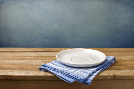 Empty plate on tablecloth on wooden table over grunge blue background Stockfoto