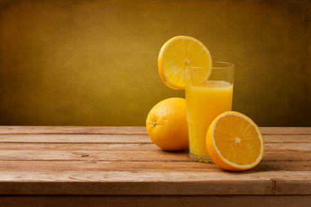 Fresh orange juice on wooden table over grunge background