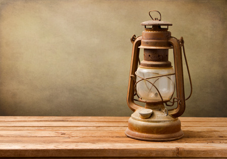 kerosene lamp: Vintage kerosene lamp on wooden table over grunge background Stock Photo