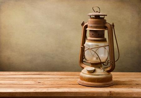 kerosene lamp: Vintage kerosene lamp on wooden table over grunge background Stock Photo
