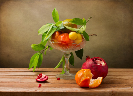 artictic: Still life with crystal vase with fruits on wooden table Stock Photo