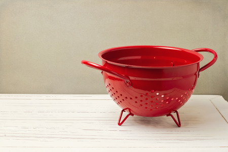 a colander: Red empty colander on white wooden table