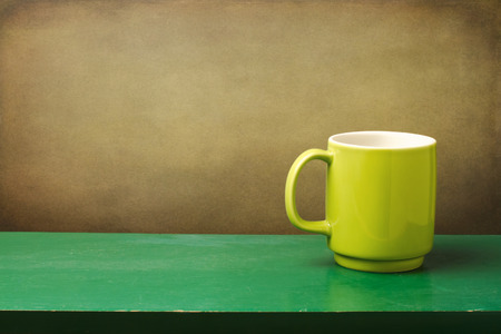 painted wood: Green mug on wooden table over grunge wall Stock Photo