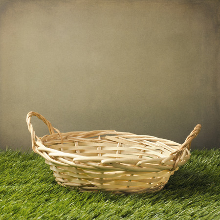 Empty basket on grass over grunge background Stock Photo