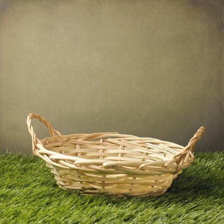 basket: Empty basket on grass over grunge background Stock Photo