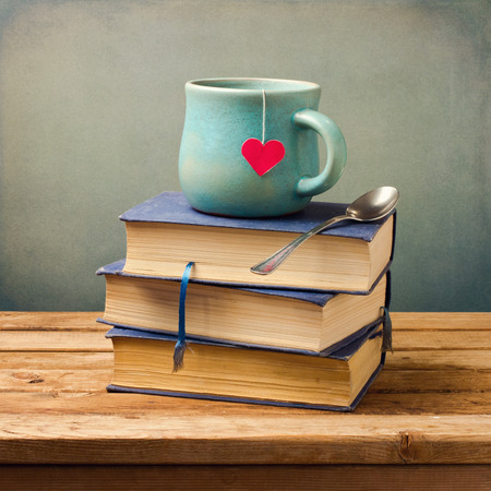 amor: Livros velhos do vintage e copo com formato de coração na tabela de madeira