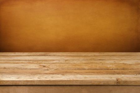 tabla de madera: Fondo de la vendimia con mesa cubierta de madera y pared marr�n del grunge Foto de archivo