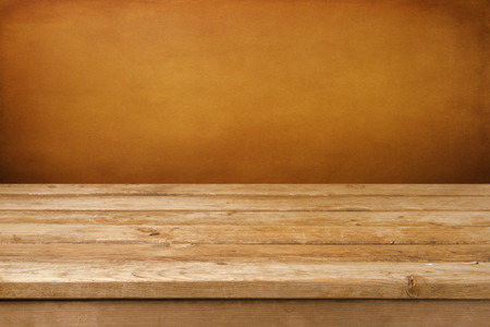 Vintage background with wooden deck table and grunge brown wall