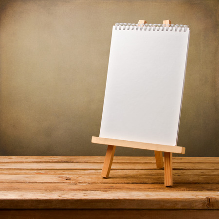 blank note book: Blank note book on easel on wooden table over grunge background