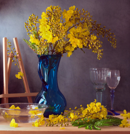 floral arrangements: Still life with beautiful yellow flowers in blue glass jug