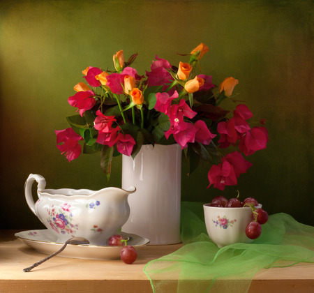 Beautiful still life with flowers and grapes Stock Photo