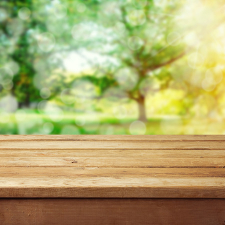 table: Empty wooden deck table with park bokeh background.