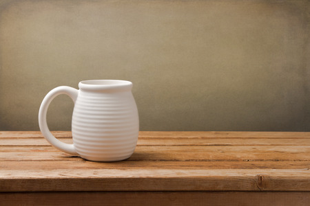 clean kitchen: White big mug on wooden vintage table over grunge background