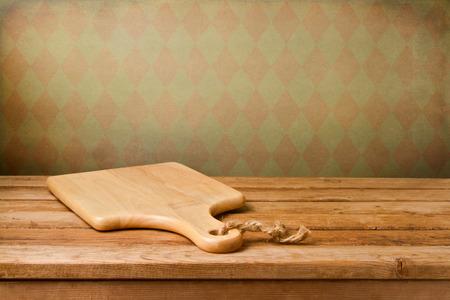 pizarra: Fondo con la tabla de cortar en la mesa de madera sobre papel pintado del vintage Foto de archivo