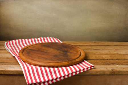Wooden board stand on tablecloth over grunge background Stock Photo