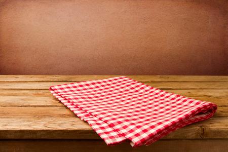 tabla de madera: Fondo retro con mesa de madera y mantel sobre la pared rugosa de color rojo Foto de archivo