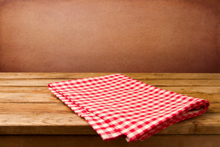 table: Retro background with wooden table and tablecloth over red rough wall