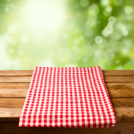 picnic cloth: Empty wooden table with tablecloth over bokeh background
