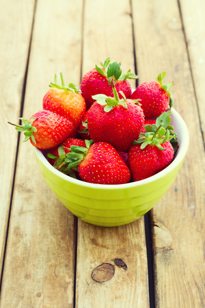 Fresh strawberries in bowl over wooden background photo