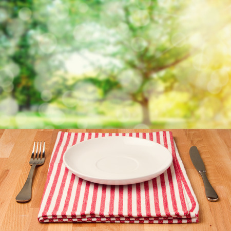Empty plate with silverware on wooden table over bokeh background