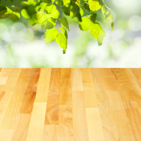 Empty wooden table over leaves bokeh background photo