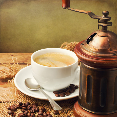 Vintage coffee grinder and coffee cup over wooden background photo