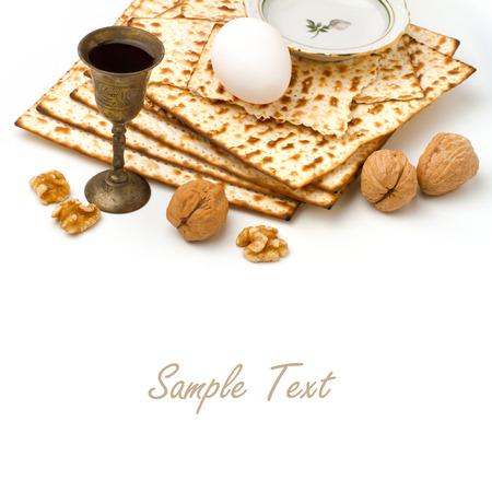 jewish holiday: Matzo, egg, walnuts and wine for passover celebration on white background Stock Photo