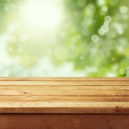 wooden planks: Empty wooden deck table with foliage bokeh background. Ready for product display montage. Stock Photo