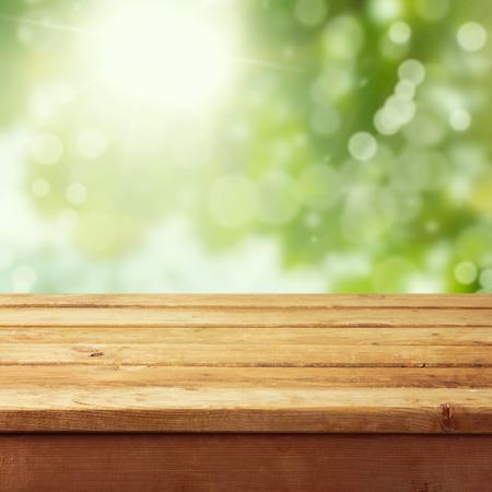 drewniane: Pusty drewniany pokład stół z liści tle bokeh. Produkt gotowy do wyświetlania montażu. Zdjęcie Seryjne