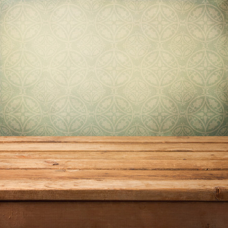 table wood: Vintage wooden deck table over grunge wallpaper with ornament Stock Photo