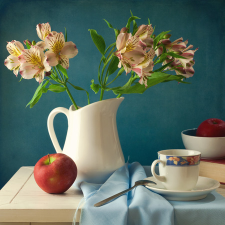 Still life with flowers and apple over blue background Stok Fotoğraf