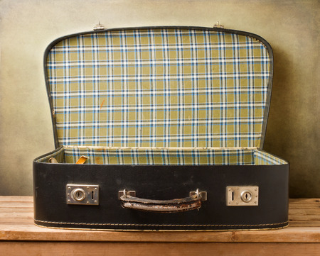 open suitcase: Empty vintage open suitcase on wooden table over grunge background Stock Photo